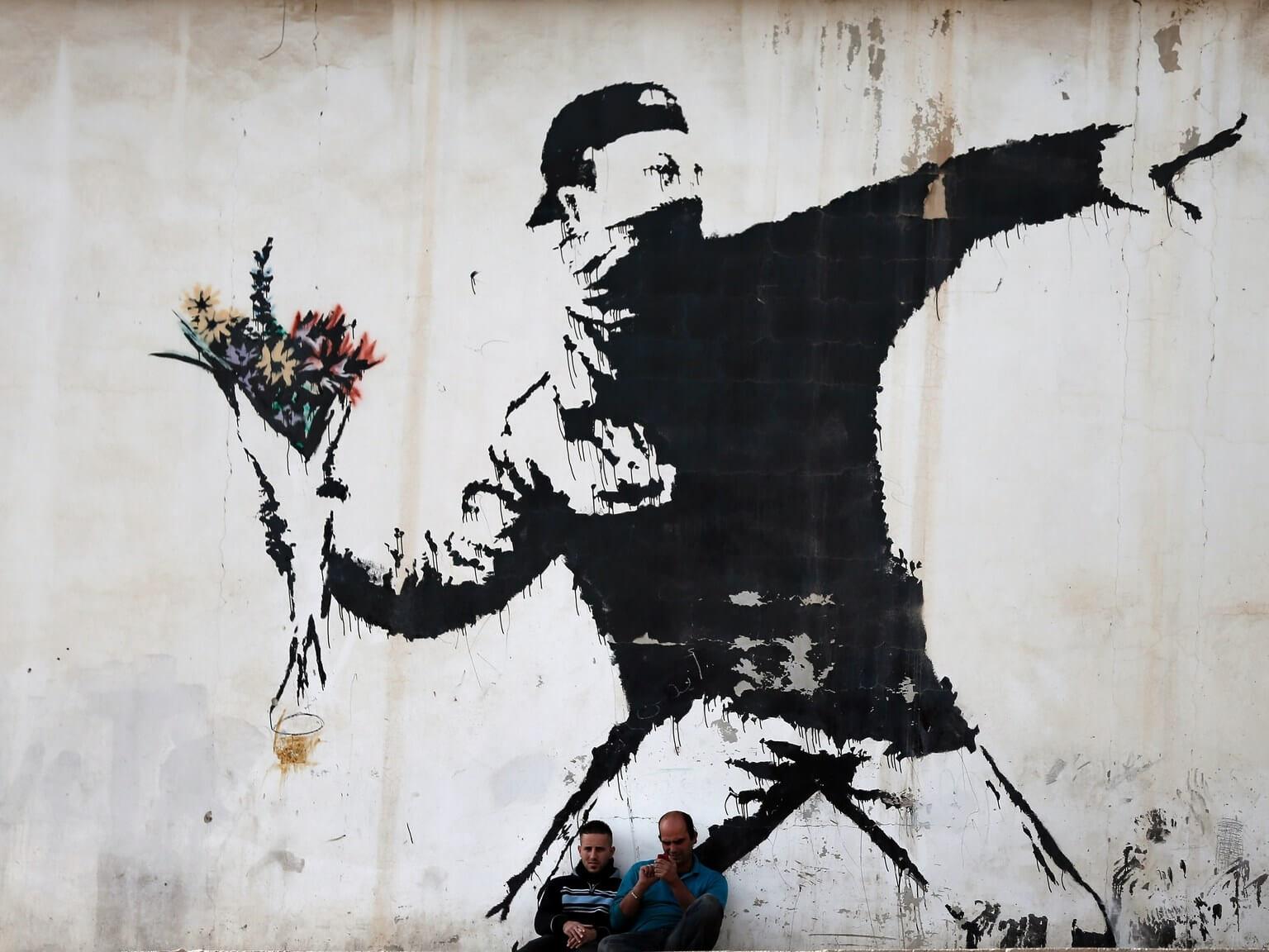 Joven lanzando flores de Banksy