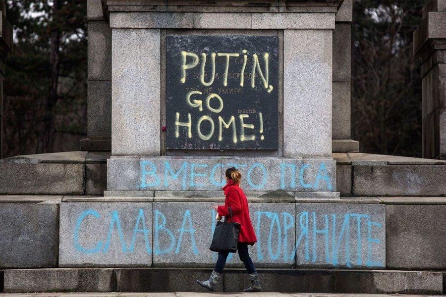A woman walks past graffiti reading Putin go home on the Soviet Army Monument in Sofia, Bulgaria