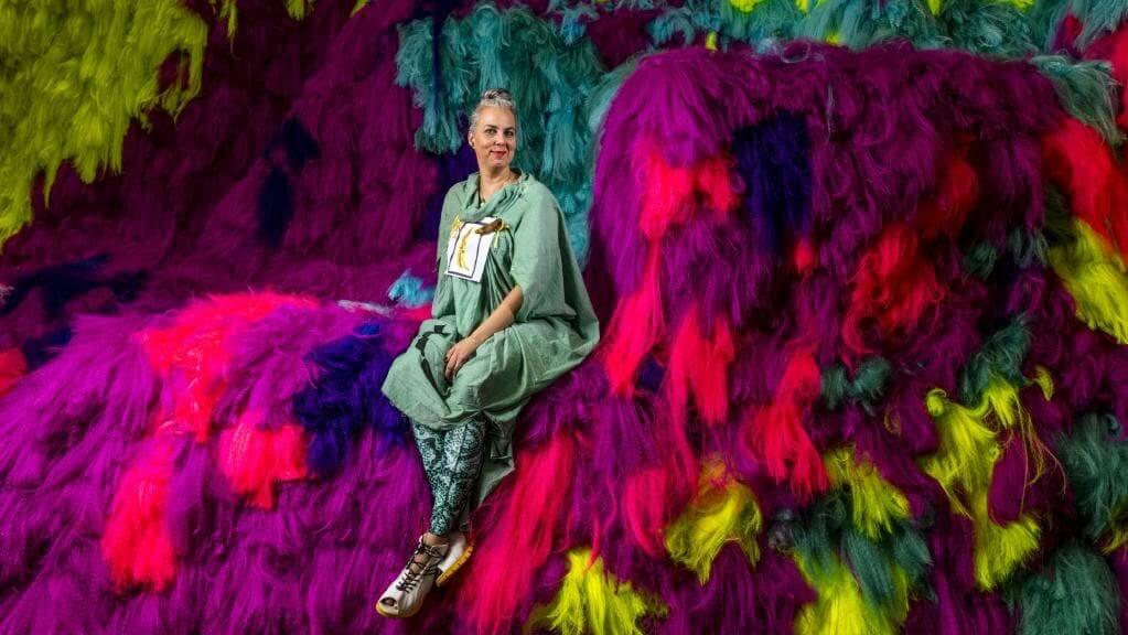 Artista Shoplfiter sentada en sus coloridas instalaciones Neverscape hecha con cabello