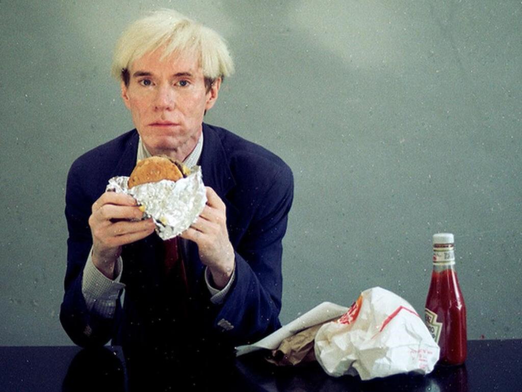 Foto de Andy Warhol comiendo una hamburguesa