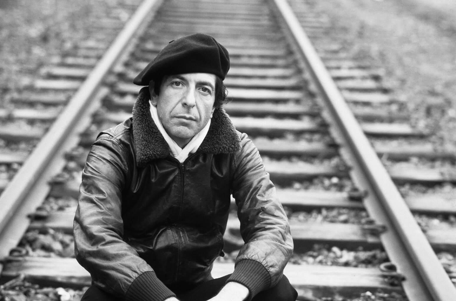 Fotografía de Leonard Cohen sentado en las Vías de un tren