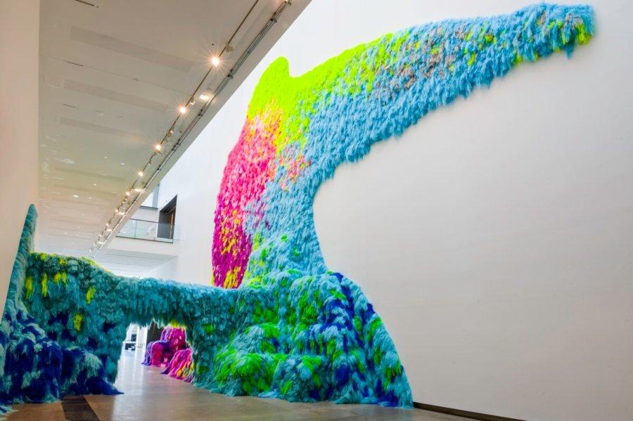 Instalación Neverscape de Shoplifter hecha con cabello de colores sobre la pared blanca