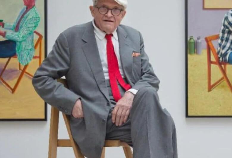 Retrato de David Hockney sentado en una galería frente a sus obras