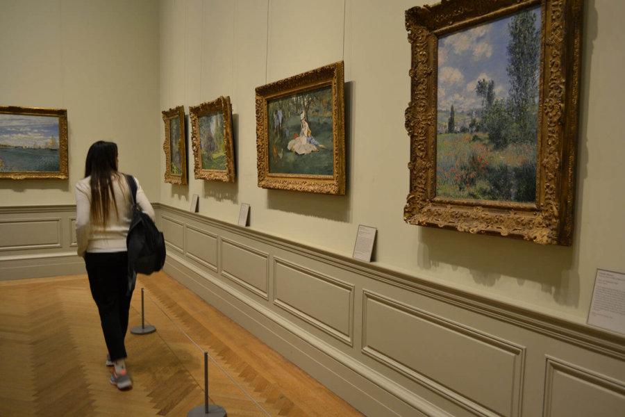 Foto de persona viendo obras en el museo