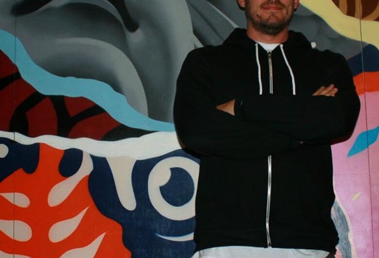 El artista Tristan Eaton posando frente a uno de sus murales