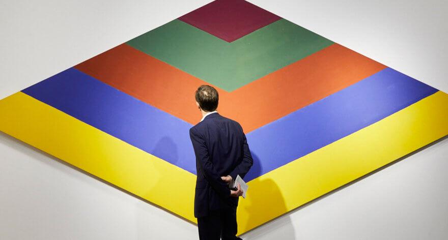 foto de un hombre viendo una obra colorida y geométrica - México presente en el Art Basel