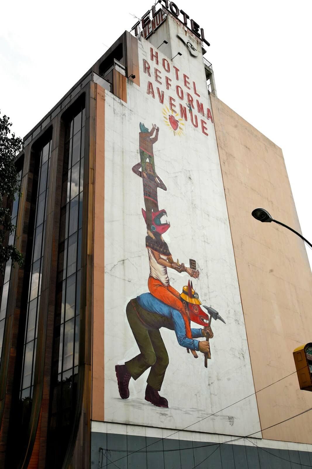 Personajes haciendo un totem sobre mural