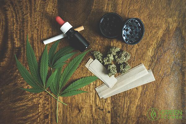gotero con aceite de cbd, papel para forjar, marihuana, planta de cannabis y grinder