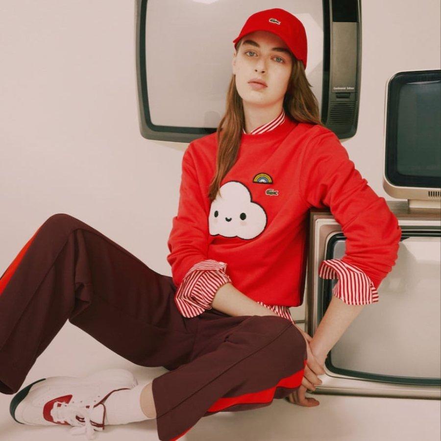 Mujer sentada recargada sobre un televisor, ella está vestida de color rojo con una sudadera y gorra de la colección de Lacoste y FriendsWithYou