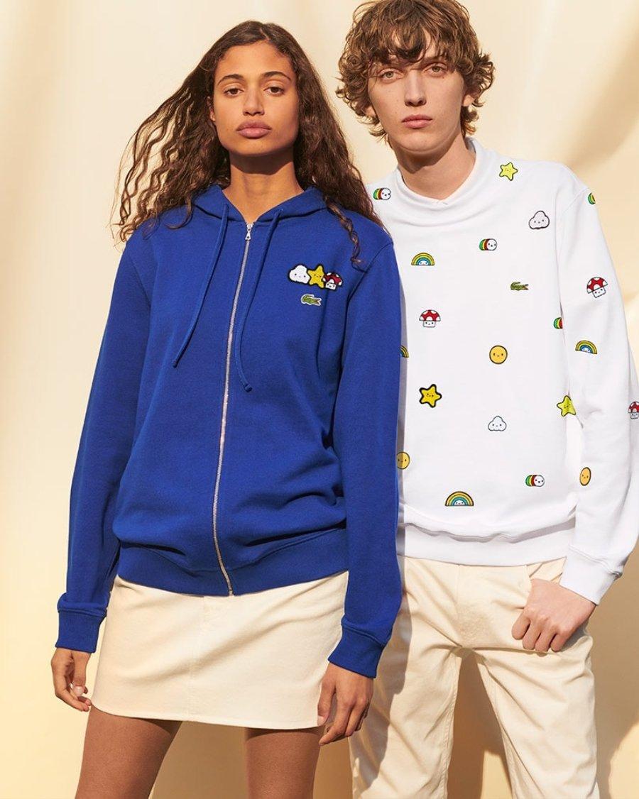 Hombre y mujer vistiendo sudaderas color azul y blanco de la colección de Lacoste y FriendsWithYou