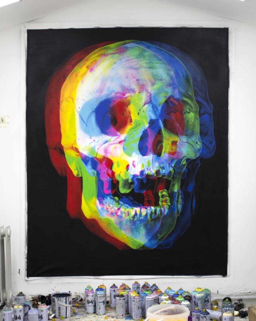 imagen de un cráneo de colores y latas de pintura de colores en la parte de abajo
