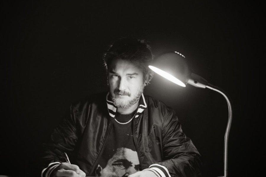 Retrato del rapero Kase O mientras sescribe bajo la luz de una lampara