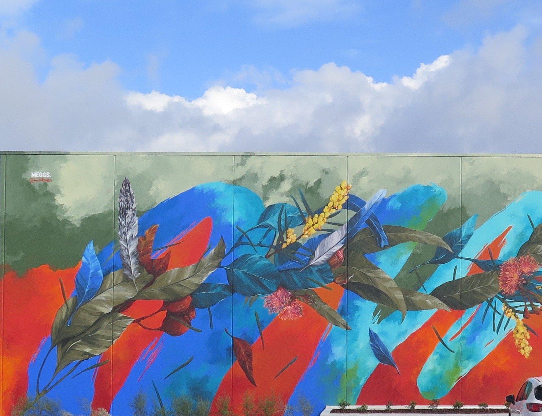 mural con hojas de plantas y plumas mezcladas entre fuego, aire y agua