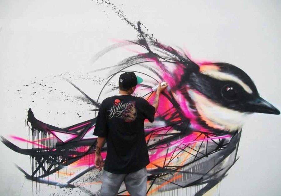 Graffitero pintando mural de pájaro