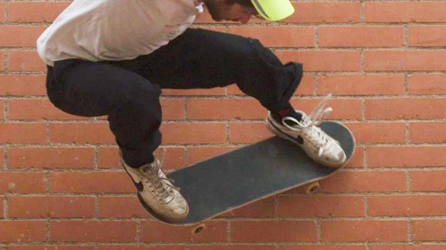Skater raspando con la tabla una pared