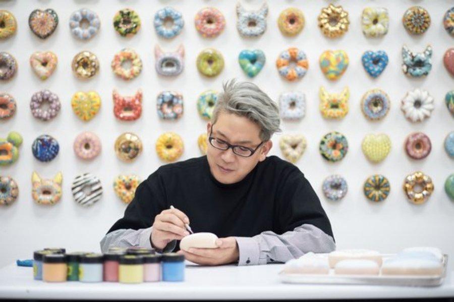 Jae Yong Kim en proceso creativo durante una exposición de sus donas en New York