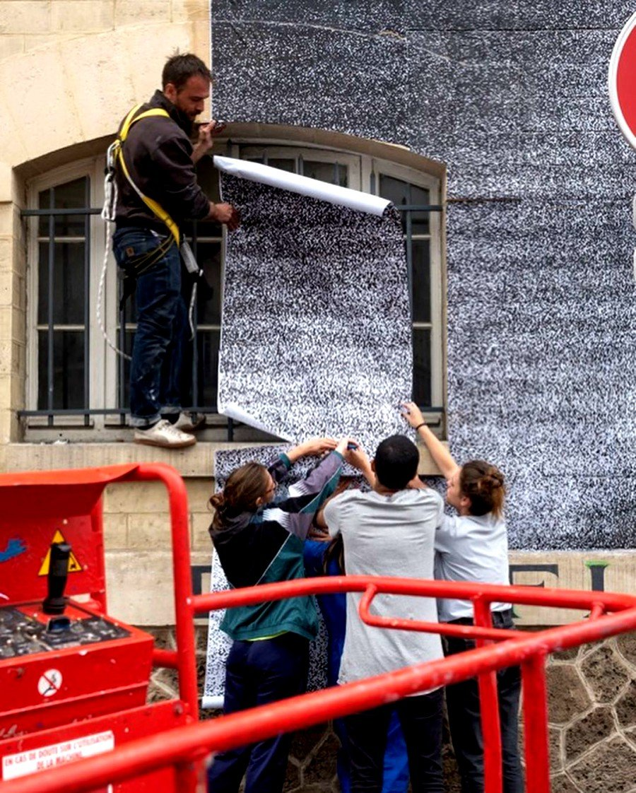 people assembling the paper of JR's mural in a Paris building