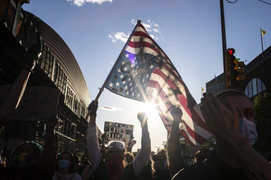 Manifestante agarrando una bandera de los E.E.U.U. en protesta