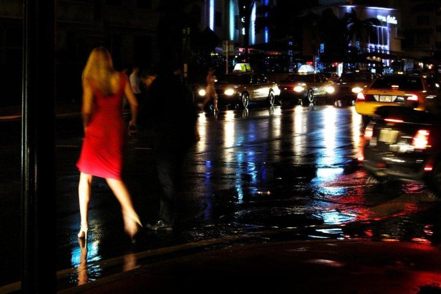 Personas cruzando una calle de noche y una avenida con carros