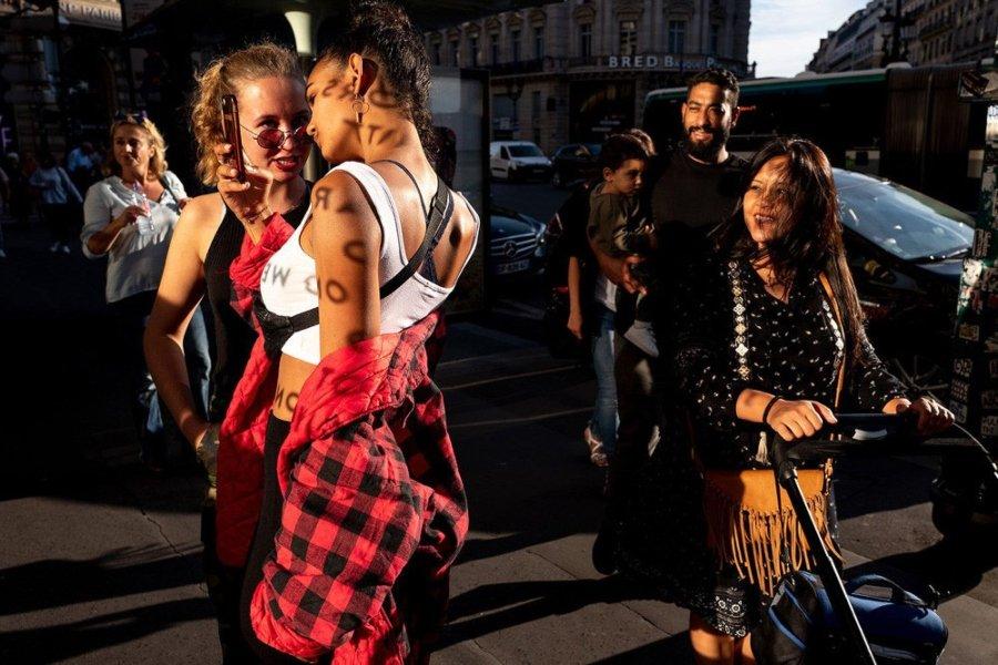 Mujeres tomándose selfie mientras otra mujer las observa