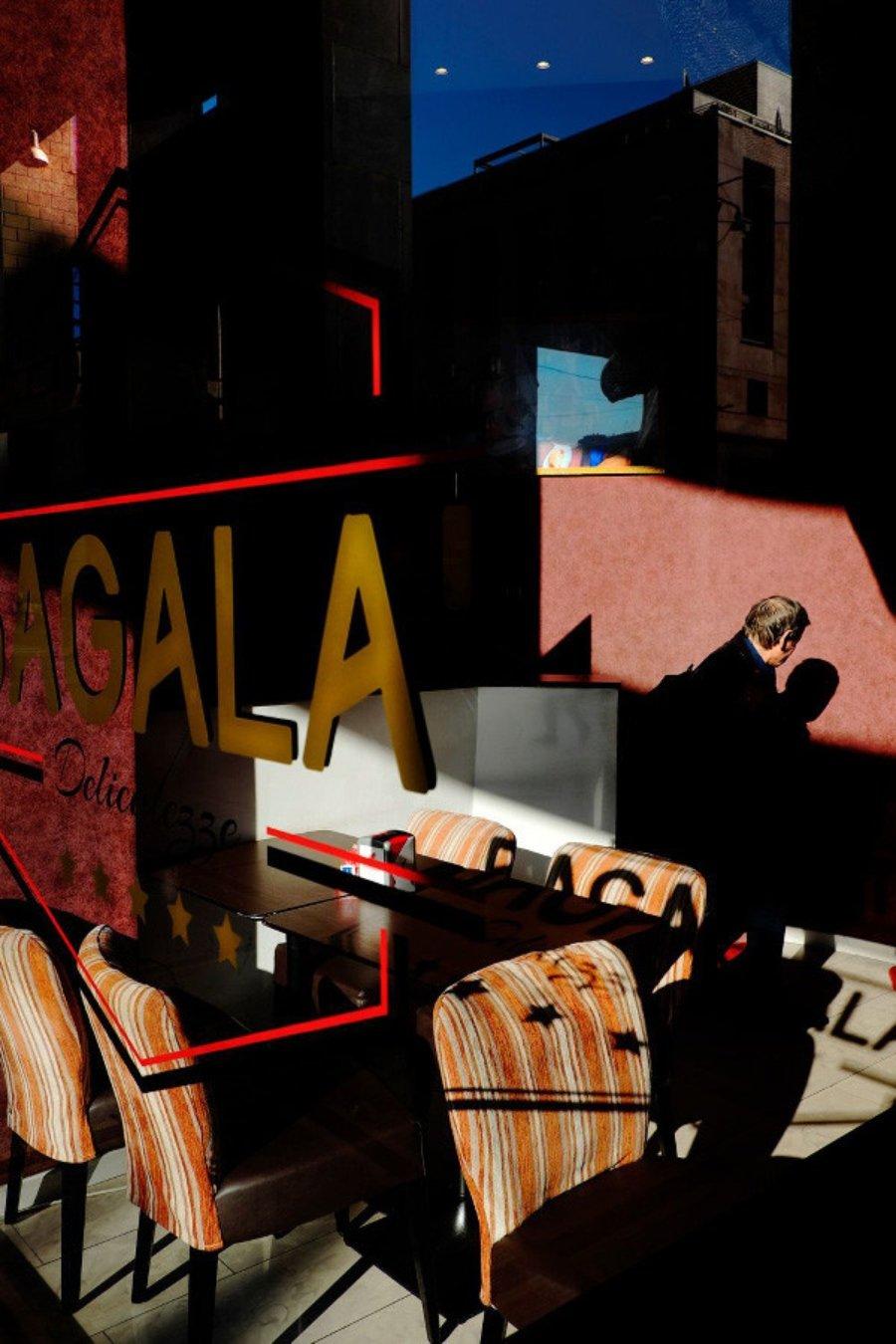 Las mejores fotografías callejeras / Hombre sentado en un restaurante con reflejos del exterior