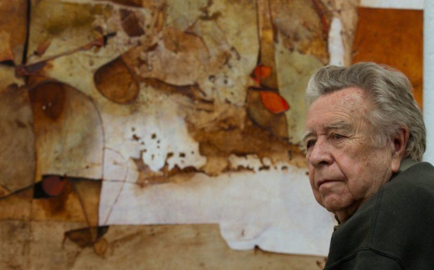 Retrato de  Manuel Felguéres frente a una de sus pinturas