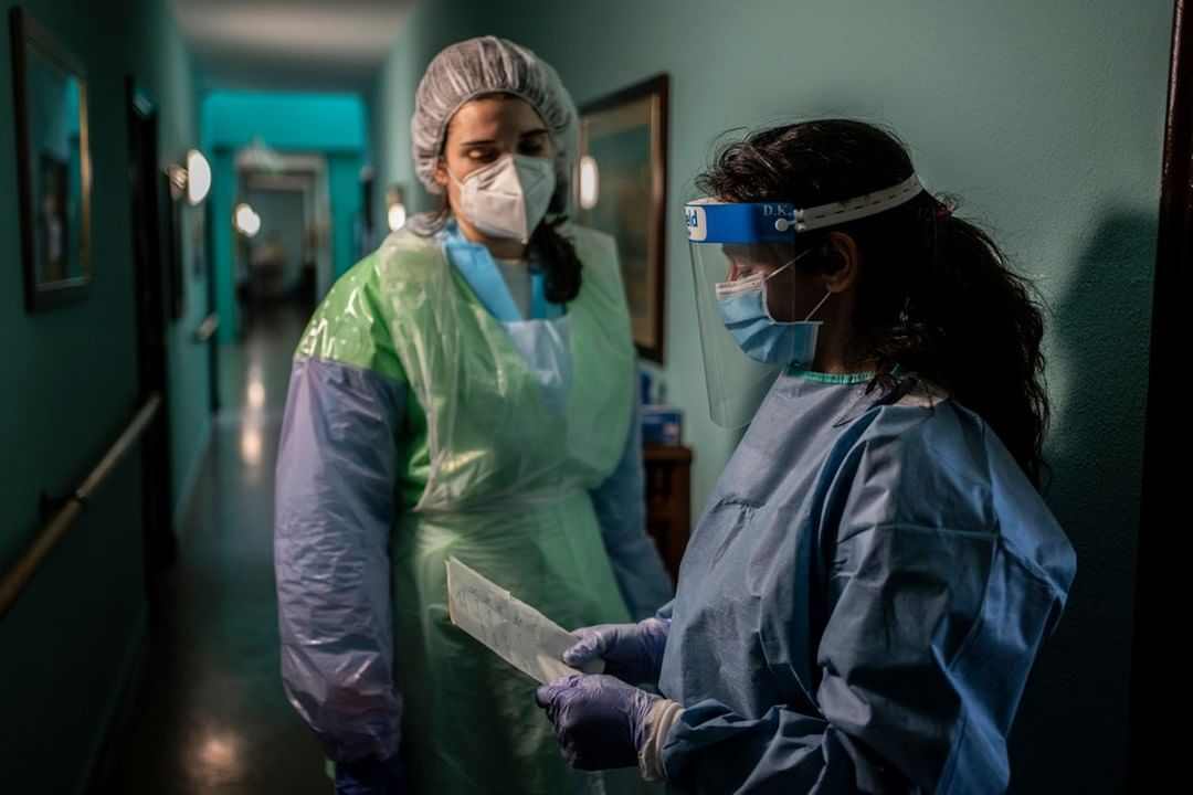 Two doctors in the hallway of a hospital with a mask, suit and protective mask read a medical report; Doctors Without Borders and All City Canvas form alliance in United With Distance