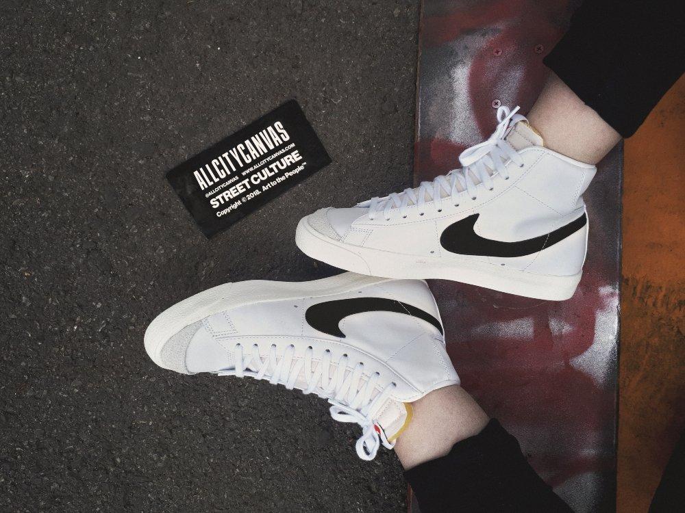 Sneakers Nike Blazer sobre una patineta de skate con un sticker de All City Canvas a un costado