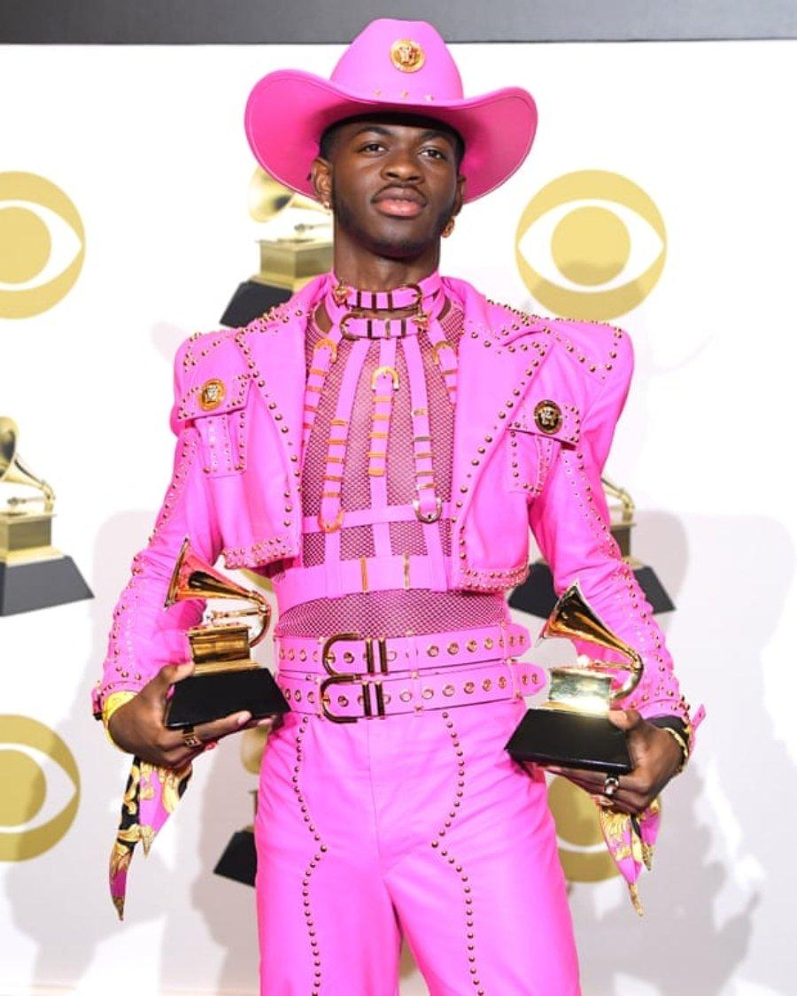 Lil Nas X vestido de violeta sosteniendo dos Grammy; él es uno de los artistas homosexuales