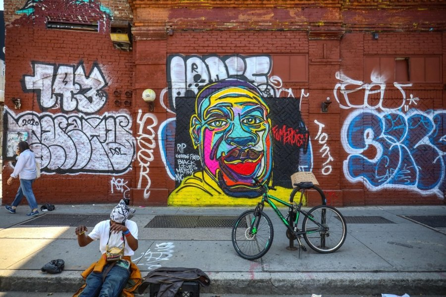 Perona sentada en el piso y detrás suyo un mural en honor a George Floyd en Soho