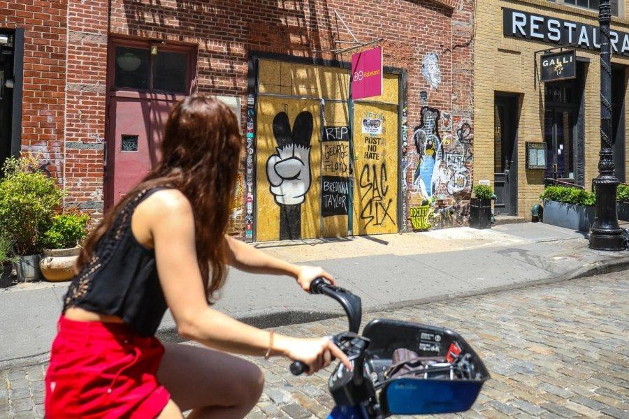 Mujer en bicicleta mirando los murales en Soho