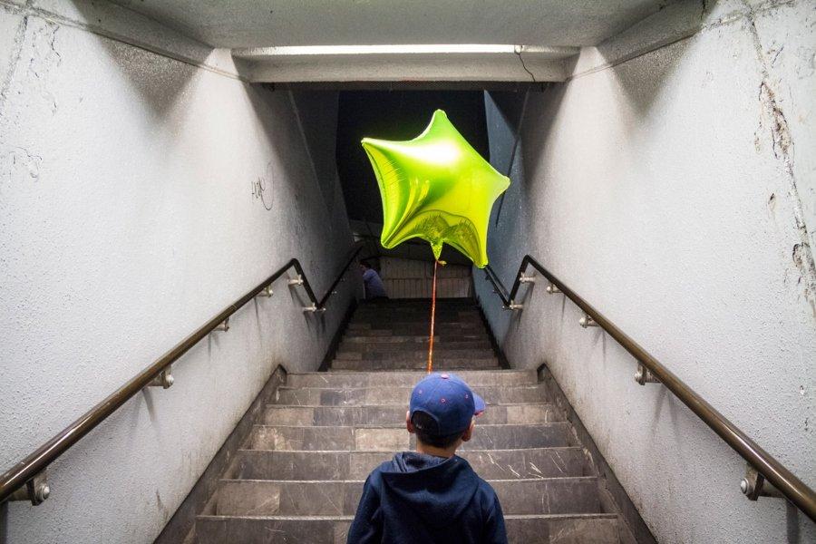 Niño con globo bajando las escaleras del metro, parte de Tiempos Muertos de sonia Madrigal