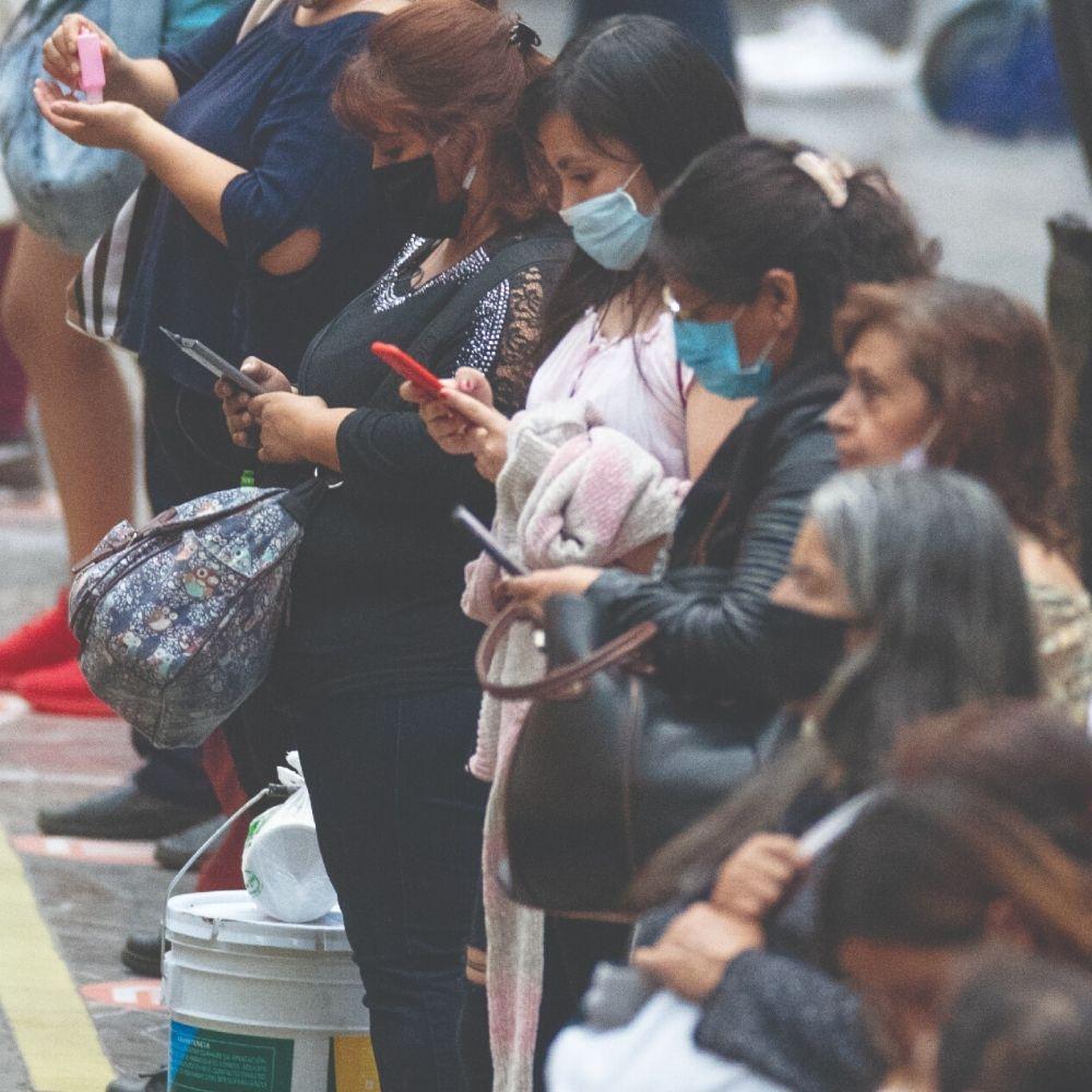 mujeres con cubrebocas mirando su celular, esperando el metro en Pantitlán, Ciudad de México