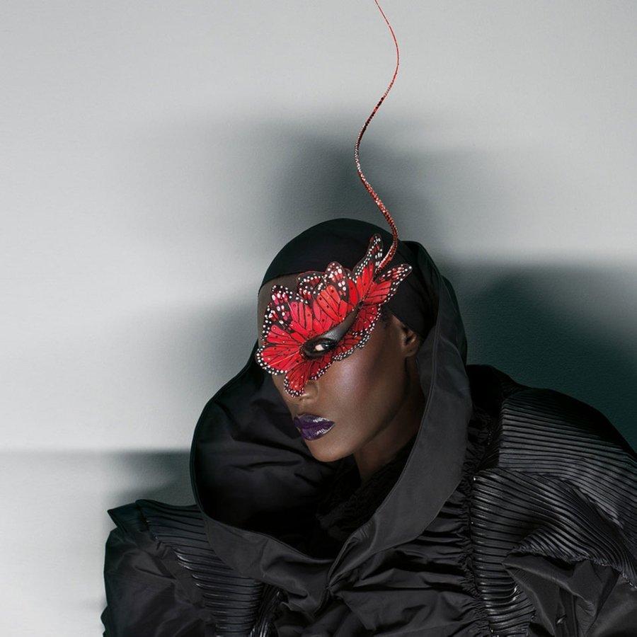 Grace Jones con una traje negro y un antifaz rojo