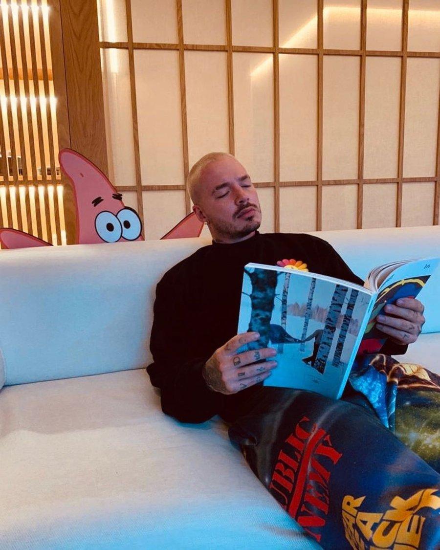 J Balvin leyendo una revista y atrás Patricio