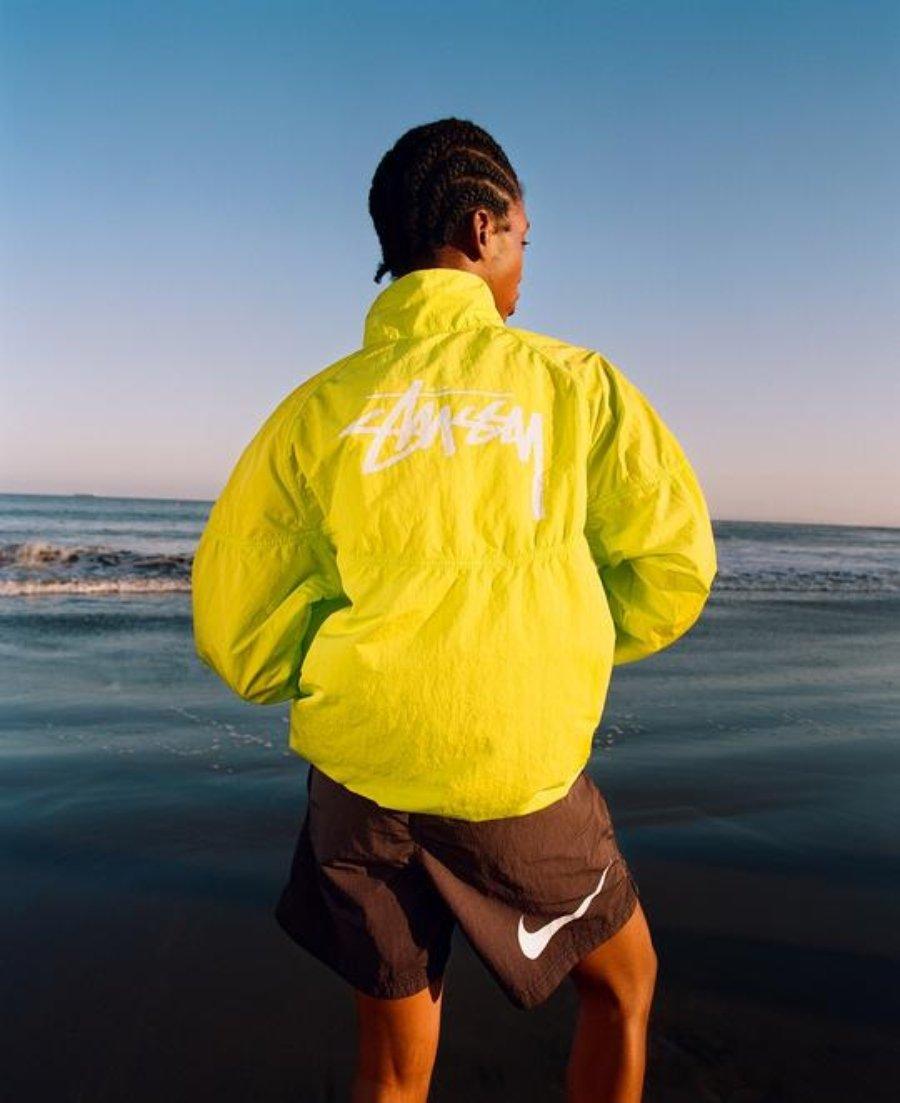 Rompevientos amarillo y short negro con los tenis exclusivos de la colección Nike y Stüssy