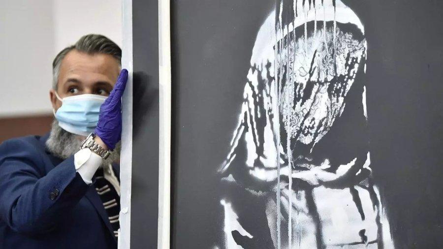 Oficial presentando la obra de Banksy después de su robo