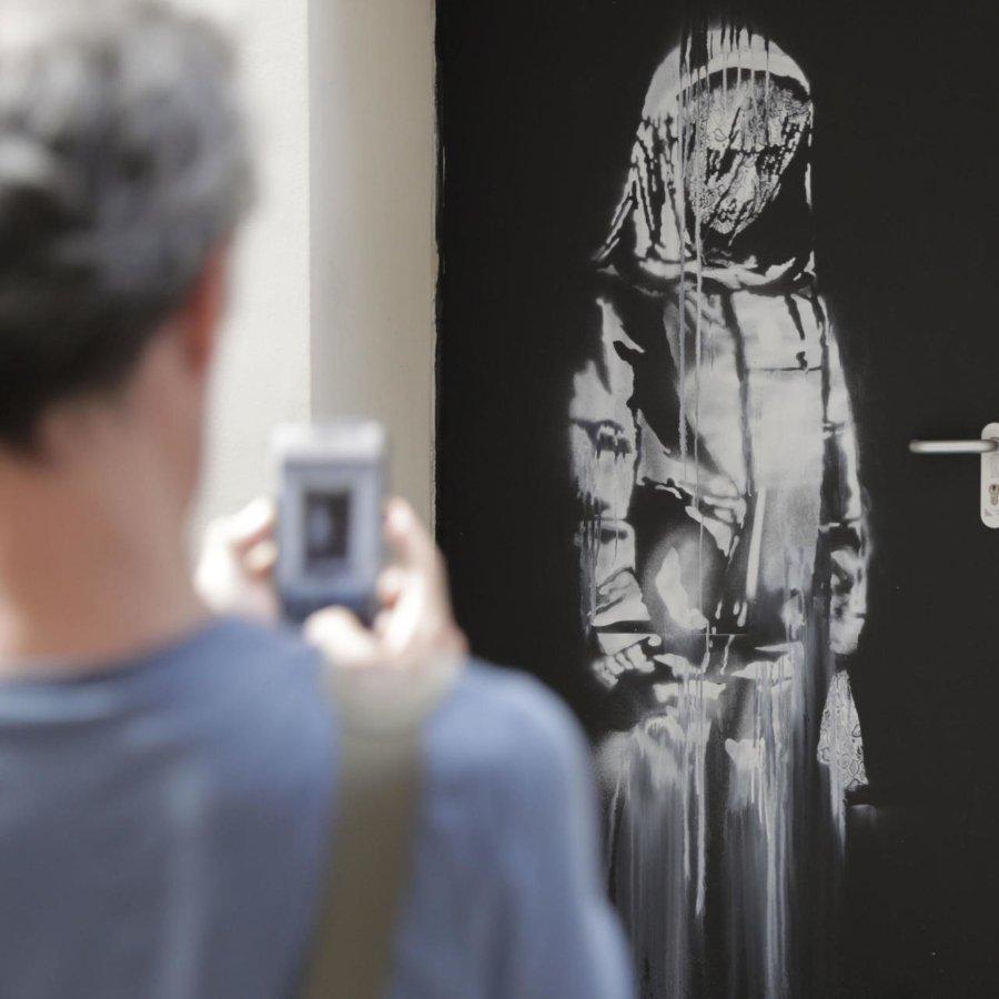 Persona tomando foto a la obra de Banksy en París
