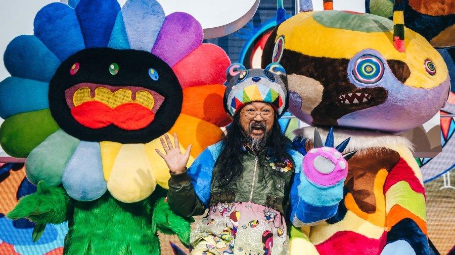 Takashi Murakami con las manos abiertas frente a sus art toys