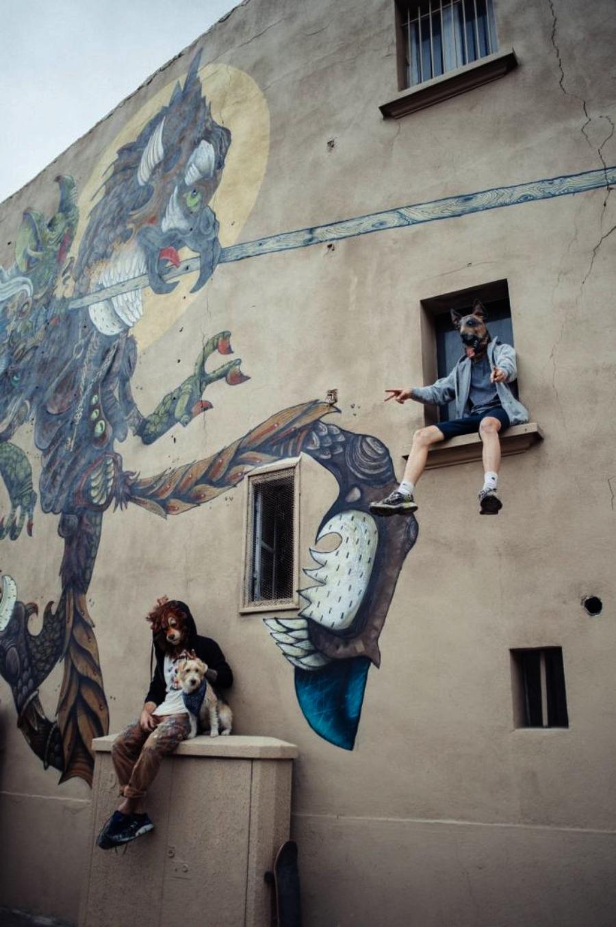 artista sentado en una escalera con mural al lado