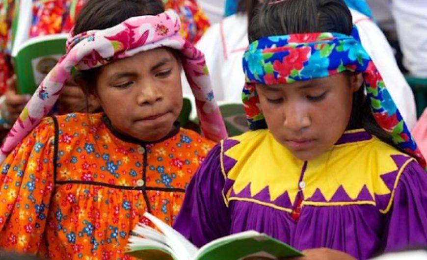 Niñas indígenas leyendo un libro