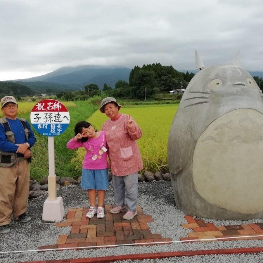 Familia posando junto a la escultura del personaje de Studio Ghibli