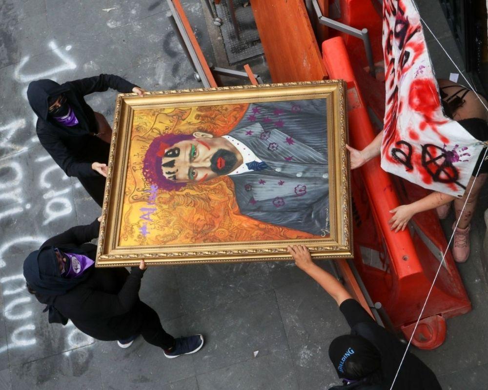 Personas encapuchadas sostienen cuadro de Francisco I. Madero vandalizado