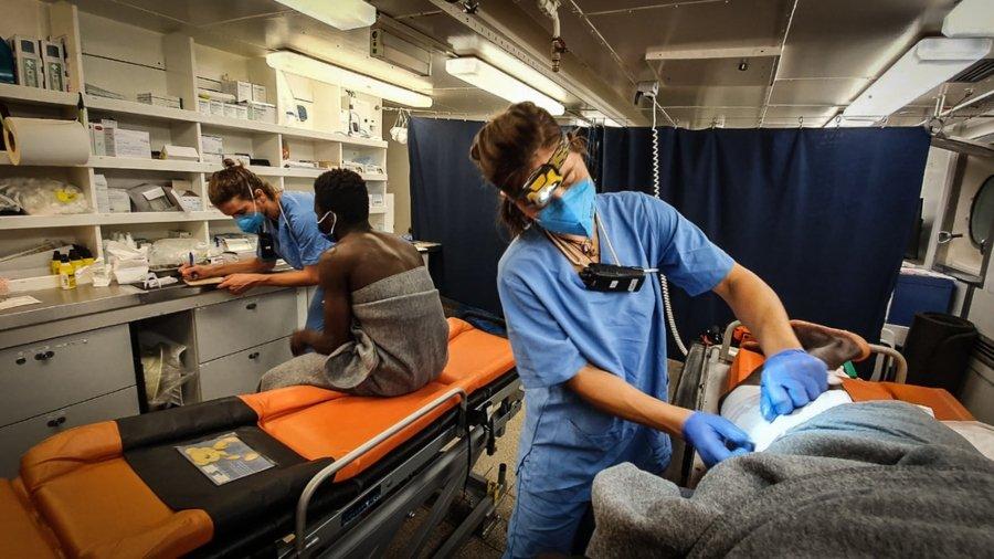 Enfermera atendiendo a migrante rescatado del barco de Banksy