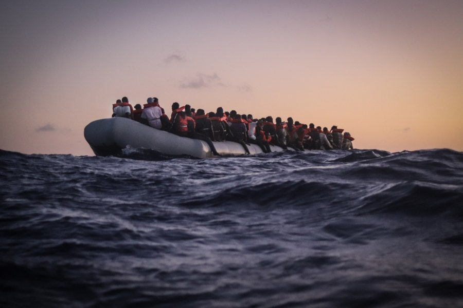 Migrantes navegando en bote hacia Italia