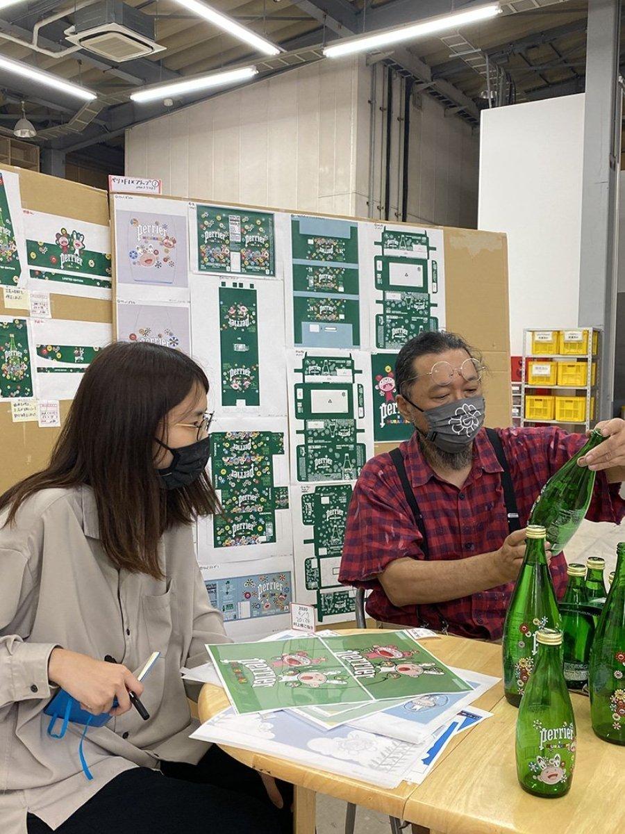Takashi Murakami sosteniendo botellas