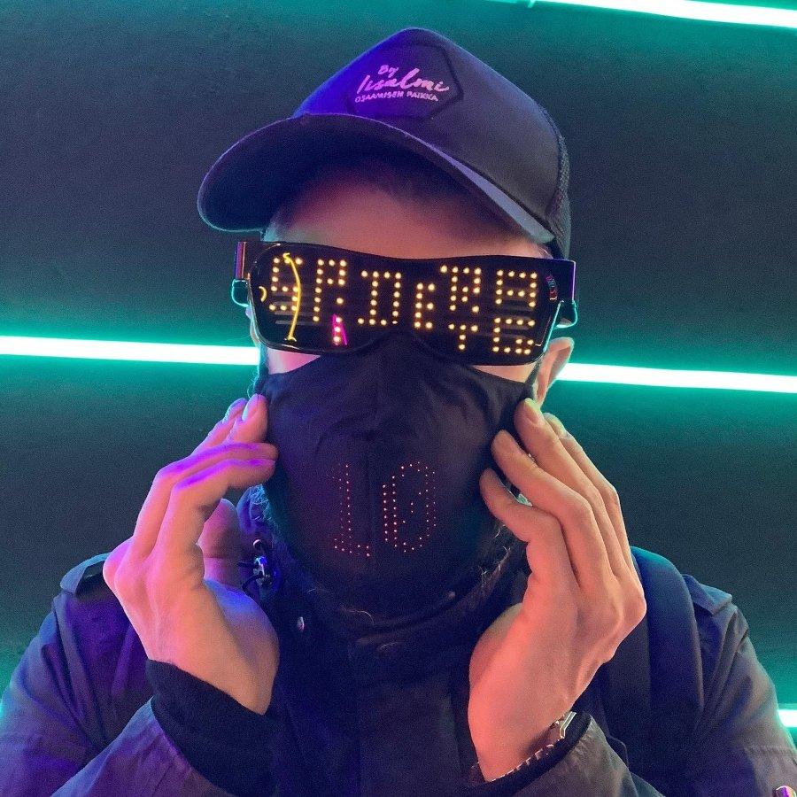 Retrato de Spidertag, hombre con gafas oscuras y luces, vistiendo una gorra con letras rosas y mascarilla negra de tela con el número 10.