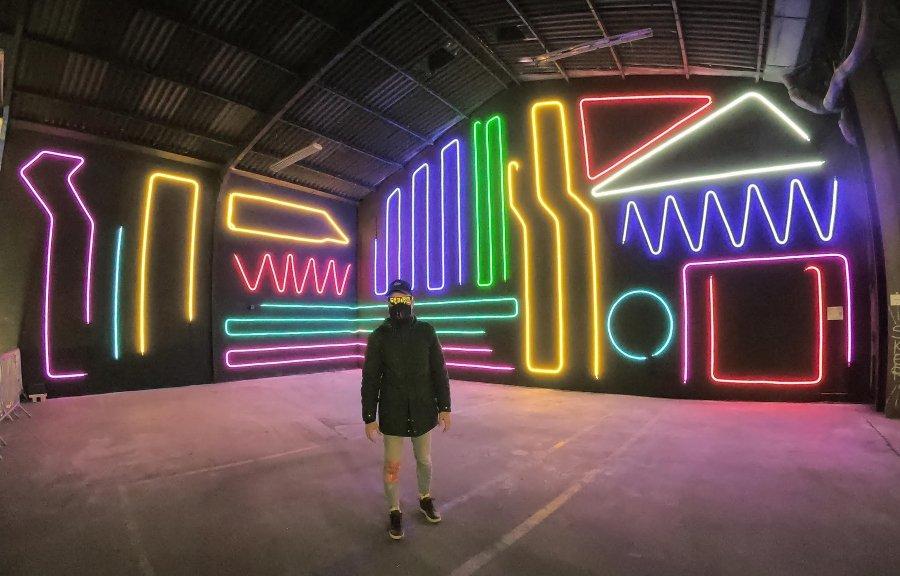 Hombre parado frente a obra de arte interactiva con luces neón