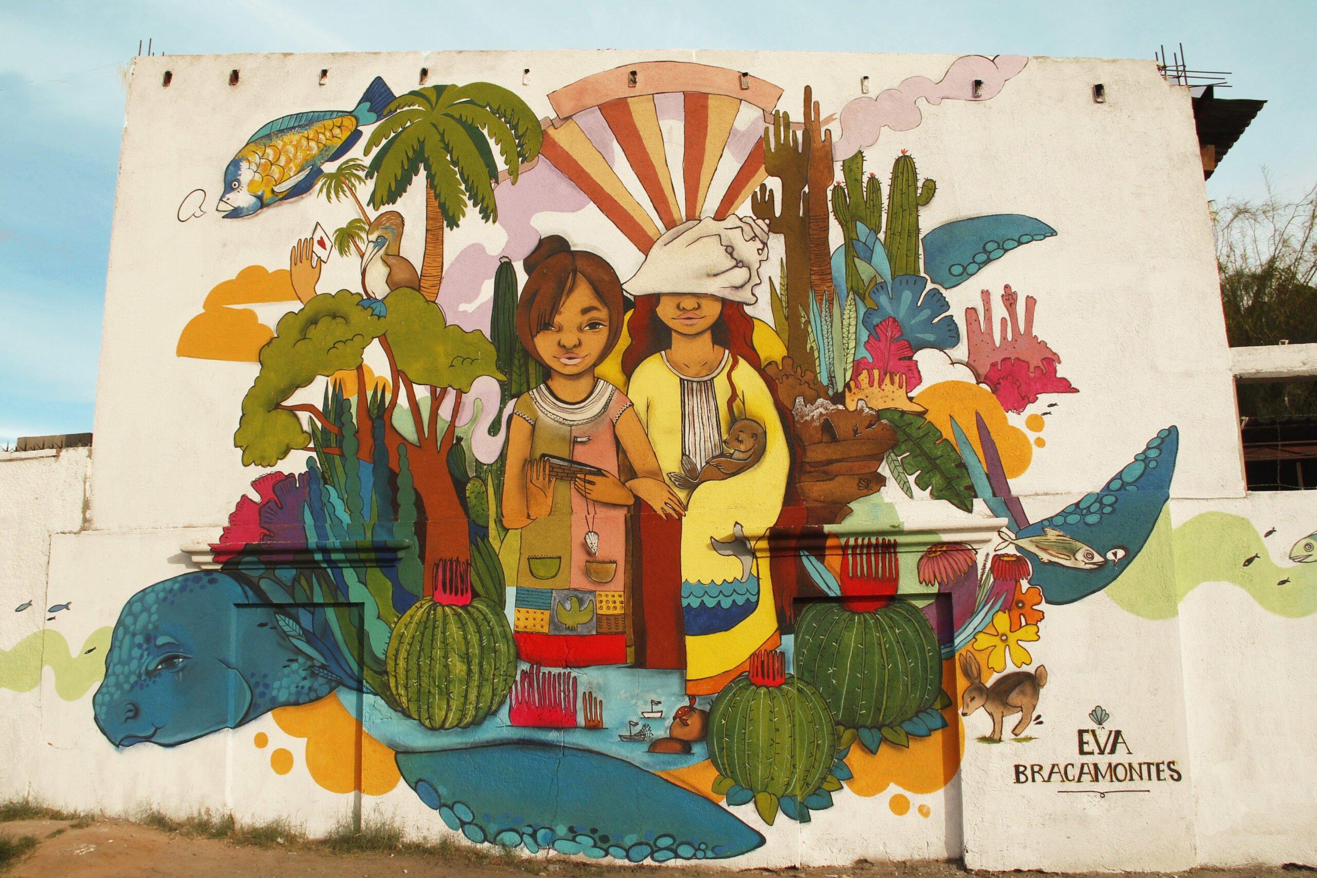 mural de Eva Bracamontes que muestra a dos mujeres en medio de varios ecosistemas y rodeadas de animales