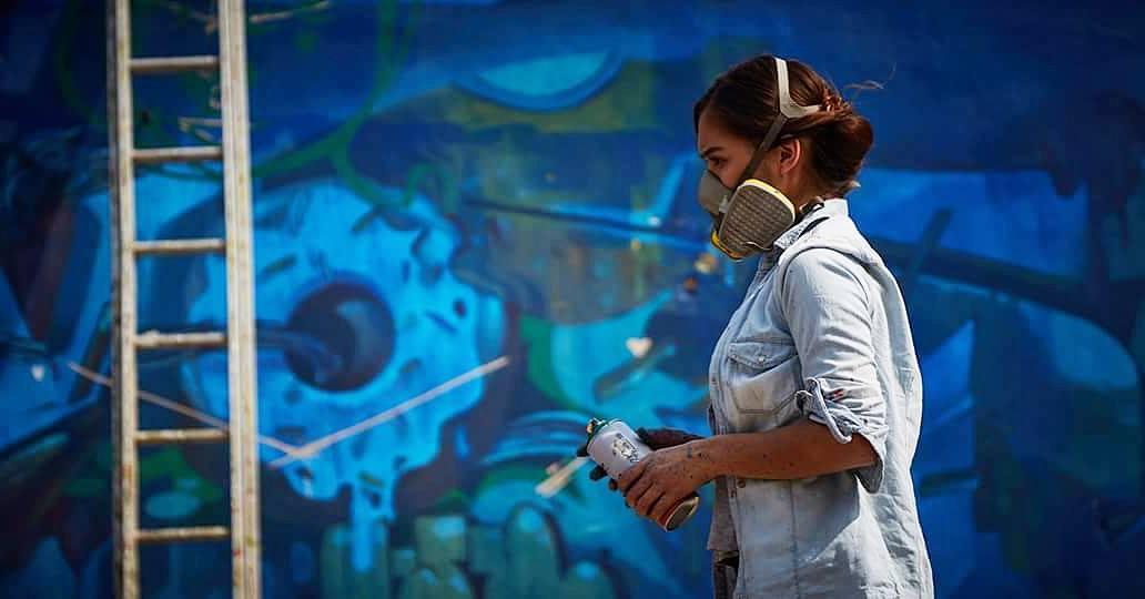 fotografía de Eva Bracmontes con mascarilla sosteniendo una lata de pintura
